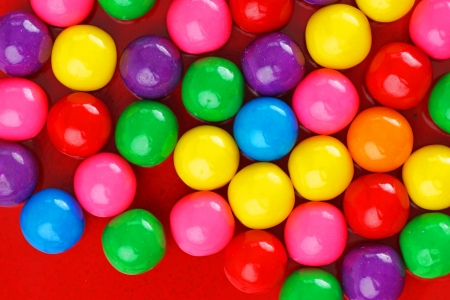 Fun and colorful gumball or bubble gum background on red ceramic