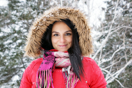 Portrait of beautiful young woman with red winter coat outdoors lookin at camera photo
