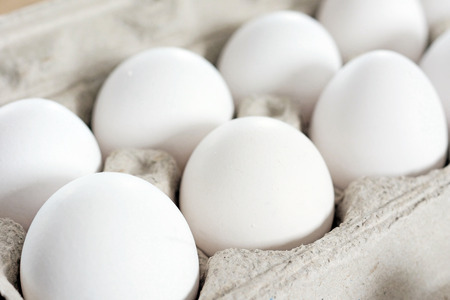 food staple: White eggs in recycled cardboard container or crate, food staple. Stock Photo