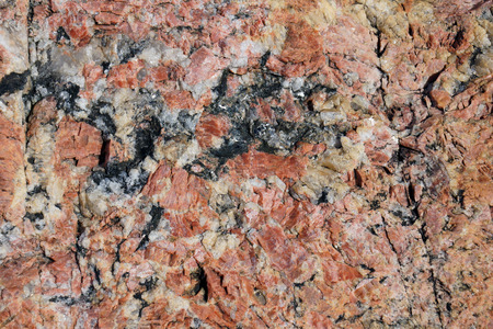 inclusions: Geology background: red or pink granite with white quartz and black mica inclusions Stock Photo