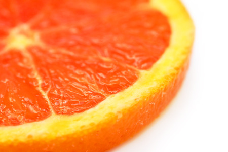 Slice of blood red orange on an angle, shallow depth of field, over white