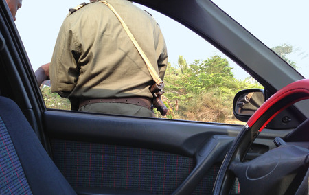 trafic: African checkpoint with armed police officer looking at driver