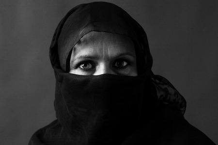 Dramatic black and white portrait of a veiled middle-aged muslim woman with strong gaze            photo