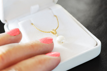 Woman fingers with pink nail polish on jewelry box with gold necklace with white pearl, gift and love concept photo