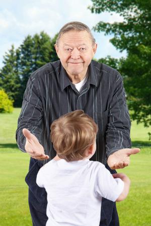bending down: Feliz el hombre mayor o abuelo agachado con los brazos abiertos para dar la bienvenida nietos.