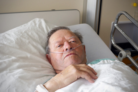 elder: Portrait of sick old man in hospital bed Stock Photo