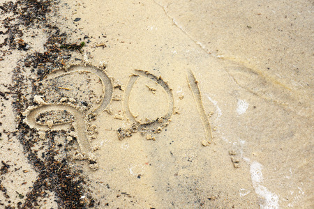 turns of the year: New year concept: year 2014 (or other number) written on the beach being washed away by a wave