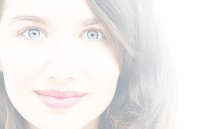 dreamy eyed: Portrait of a beautiful young woman, wide eyes and little smile, high key, white filter Stock Photo