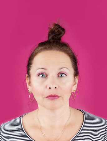 neutral face: Portrait of neutral face middle aged woman with hair bun over pink background Stock Photo