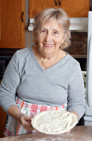 Happy senior woman or grandma showing homemade meat pie in her kitchen
