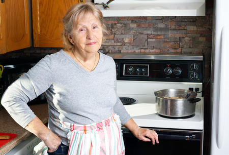 caldron: Friendly smiling grandmother or senior woman cooking in her kitchen