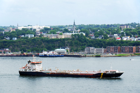 tonnes: QUEBEC CITY, CANADA - JULY, 20: Large oil tanker on the St.Lawrence river in front of Quebec city. Twenty-five million tonnes of crude oil and various petroleum products are transported on the St.Lawrence seaway. Most vessels stop at the ports of Quebec a