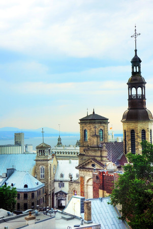 crucifixes: Beautiful historical Quebec city, Canada, cityscape with church and old building over the water