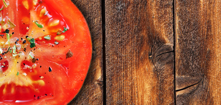 Red tomatoe with herbs on weathered wood background