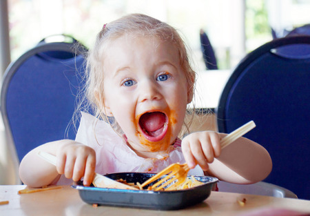 mess: Funny little blond girl eating pasta and making a mess