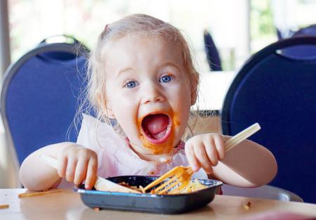 Grappig klein blond meisje het eten van pasta en het maken van een puinhoop