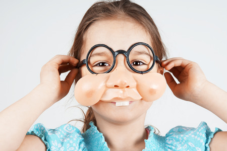 fake: Little girl with funny fake nose and round glasses Stock Photo
