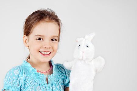 mignonne petite fille: Cute petite fille jouant avec la marionnette de lapin main