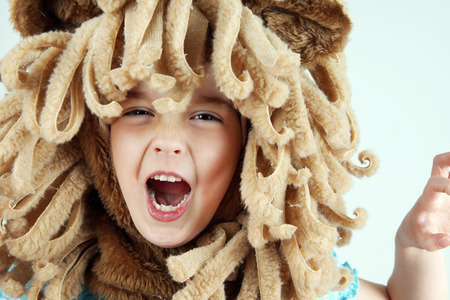 mane: Little girl with lion mane costume roaring, playing Stock Photo