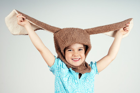 Little girl playing with rabbit costume showing big ears
