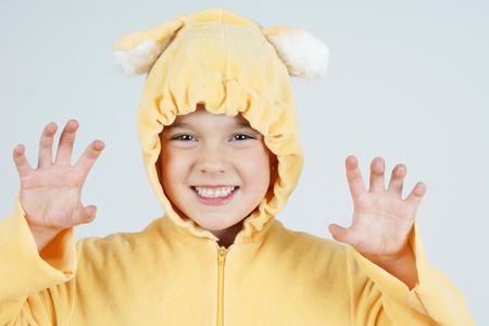 growling: Cute little girl in teddy bear costume making scary face