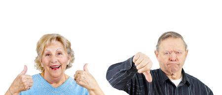 contradiction: Senior woman giving two thumbs up and grumpy man thumb down