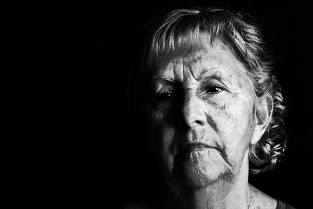 sad face: Dramatic black and white portrait of a senior woman looking away Stock Photo