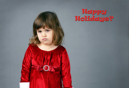 upset: Cute little girl in red Christmas dress sulking and pouting Stock Photo