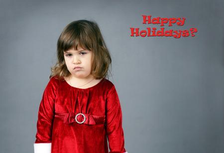 niñas pequeñas: Niña linda en rojo mal humor vestido de Navidad y haciendo pucheros