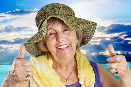 senior women: Happy senior woman at the beach two thumbs up