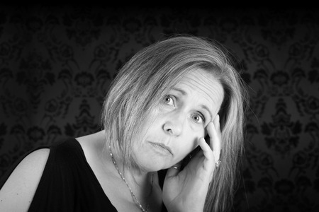 Black and white of woman looking sad on black damask Stock fotó