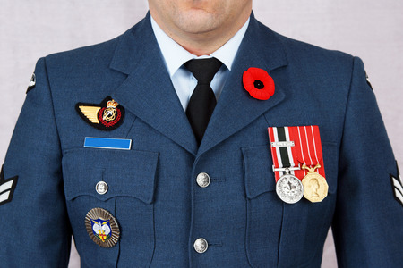 QUEBEC, CANADA - NOVEMBER 11, 2016: Air force corporal wearing red poppy lapel pin on Canada's remembrance day, November 11, 2016. Memorial day observed in the Commonwealth to remember the dead of World War 1. Sajtókép