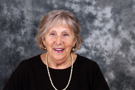 Happy senior woman smiling with pearl necklace