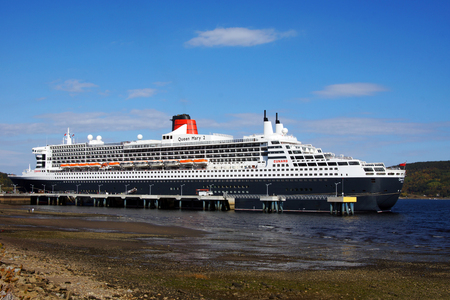 SAGUENAY, QUEBEC, CANADA - OCTOBER 8, 2016: Full view of the Queen Mary 2 cruise ship at the Bagotville wharf on the Saguenay fjord on October 8, 2016. The Saguenay flows into the St.Lawrence seaway. Sajtókép