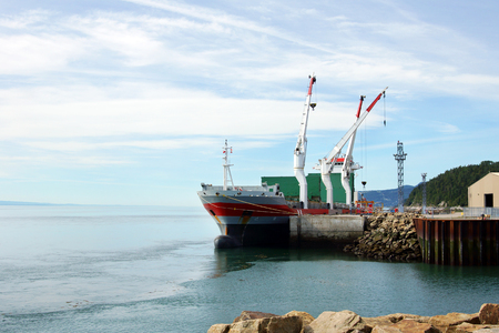 commerce and industry: Small seaport with docked cargo ship Stock Photo