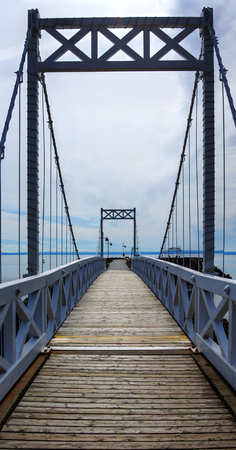 Perspective view cable and wood bridge of a small coastal town, vertical