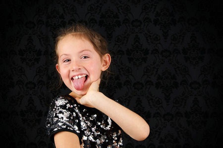 Portrait of funny little blond girl sticking out tongue 스톡 콘텐츠