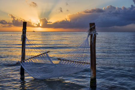 Tropical paradise, hammock over the sea at sunset