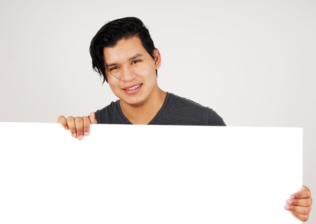 Friendly young latino man holding white blank sign Stock fotó - 98416057