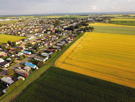 Aerial view of small town bordered by barley and corn fields