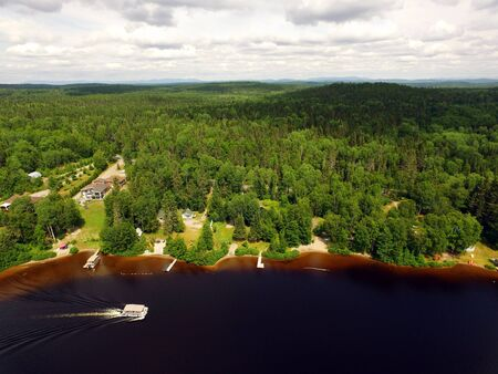 Aerial view of forest lake with cottages and ponton cruising by Stock fotó