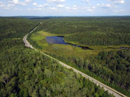Aerial view of a road going through forest and mountains with bog or marsh, Quebec, Canada