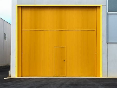 Industrial unit with lareg yellow door.