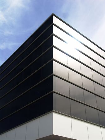 Modern glass building exterior with the sun reflected in one side. photo