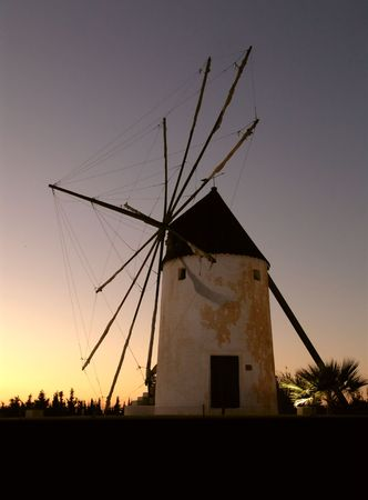 aquifer: An ancient agricultural windmill with the sails wrapped-up
