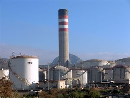Storage tanks and chimney at a petrochemical plant. Stock Photo