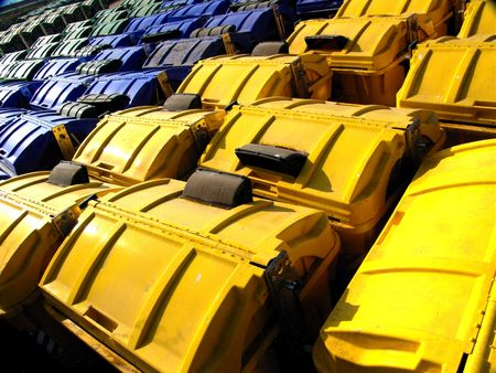 ecological problem: Numerous garbage recycling containers - yellow, blue & green. Stock Photo