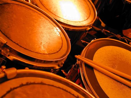 Drum kit bathed in orange light, 2 drumsticks resting on the snare drum.