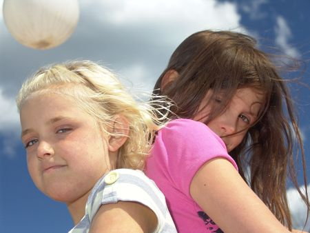 taller: Two young girls standing back to back outdoors Stock Photo