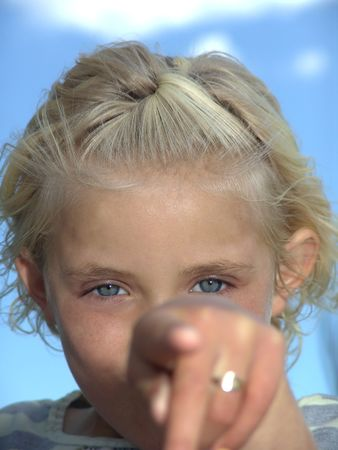 Young girl pointing finger in direction of camera photo